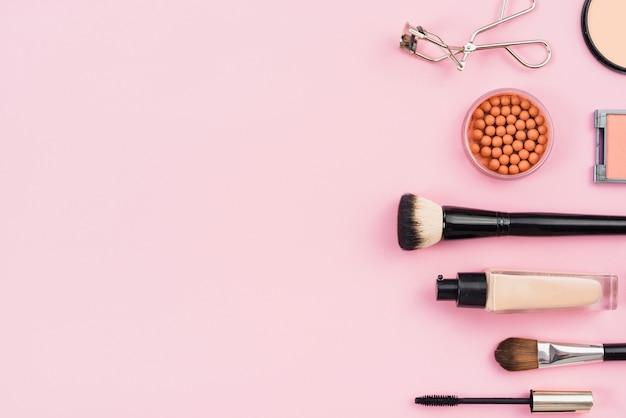 Anordnung für make-upprodukte auf rosa hintergrund Kostenlose Fotos