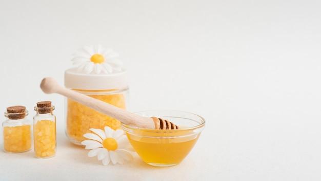 Anordnung mit honig und salzen auf weißem hintergrund Kostenlose Fotos