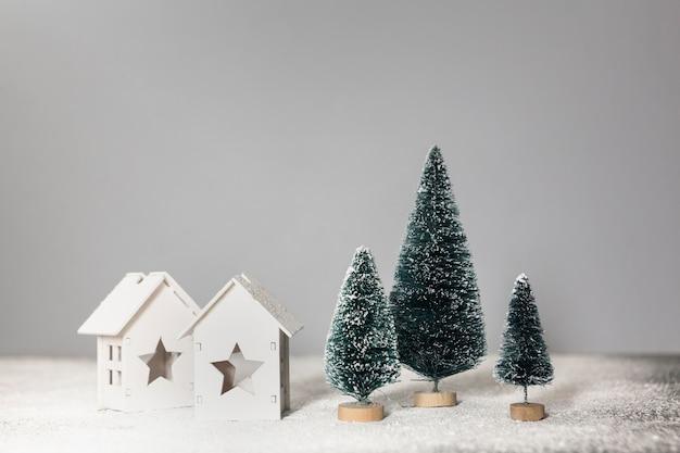 Anordnung mit kleinen weihnachtsbäumen und häusern Kostenlose Fotos