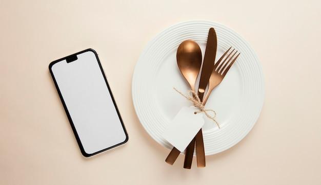 Anordnung von elegantem geschirr mit leerem smartphone Kostenlose Fotos