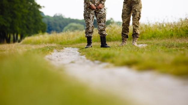 Ansicht der beine von zwei männern in den militäruniformen in den stiefeln nahe der bahn auf dem gebiet Premium Fotos