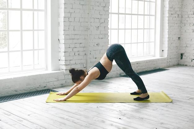 Ansicht der flexiblen jungen frau in voller länge mit schlankem körper, der in der fitnesscenterhalle trainiert, yoga macht, mit matte auf holzboden trainiert, nach unten gerichteten hund oder adho mukha svanasana-pose macht Kostenlose Fotos