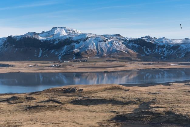 Ansicht der schneebedeckten reynisfjall-berge von dyrholaey, island Premium Fotos