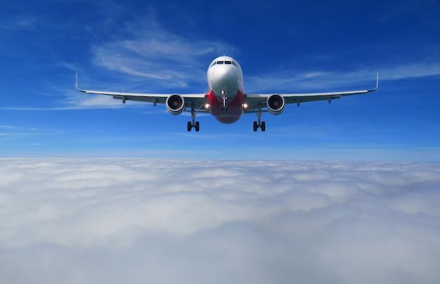 Ansicht des flugzeuges mit der vollen landungskonfiguration, die über die schöne wolke fliegt. Premium Fotos