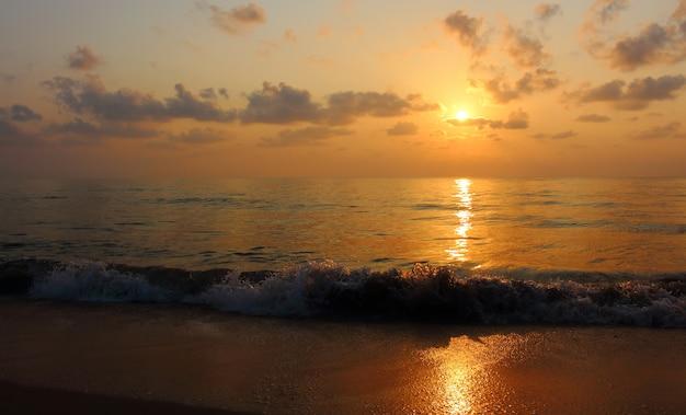 Ansicht des schönen sonnenaufgangs über dem meer auf dem himmel und sand setzen morgens auf den strand. Premium Fotos