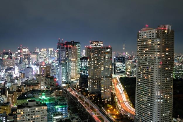 Ansicht des wolkenkratzers und des glühenden hellen verkehrs herein in die stadt nachts Premium Fotos