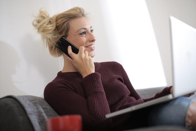 Ansicht einer schönen kaukasischen frau, die auf der couch sitzt, während sie am laptop arbeitet und spricht Kostenlose Fotos