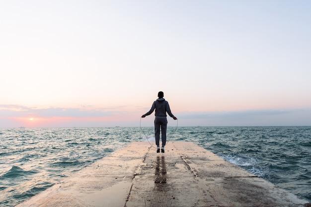 Ansicht in voller länge des jungen mannes in der sportkleidung, die mit springseil, training auf pier springt Kostenlose Fotos