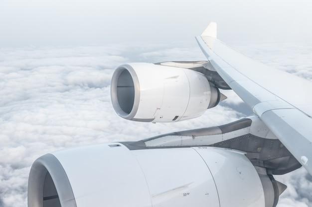 Ansicht vom flugzeugfenster und vom flügel, über flaumigen wolken, fliegen und reisendem konzept Premium Fotos