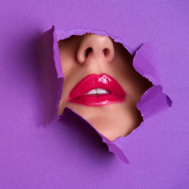 Ansicht von hellen lippen durch loch im violetten papierhintergrund. Premium Fotos