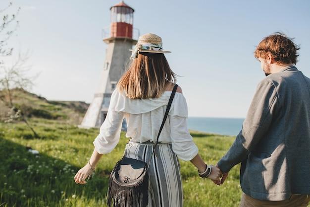 Ansicht von hinten auf hipster-indie-stil des jungen paares in der liebe, die in der landschaft geht, händchen haltend, leuchtturm auf hintergrund, warmer sommertag, sonniges, böhmisches outfit, hut Kostenlose Fotos