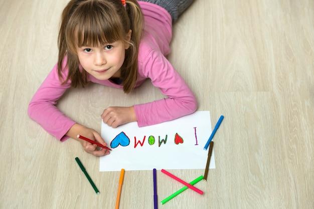 Ansicht von oben genanntem der netten kindermädchenzeichnung mit bunten zeichenstiften ich liebe mamma Premium Fotos