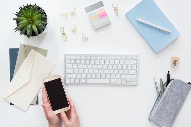 Ansicht von oben genanntem von den weiblichen händen mit handy, geschäftsarbeitsplatz mit computertastatur, flache lage des notizbuches. Premium Fotos