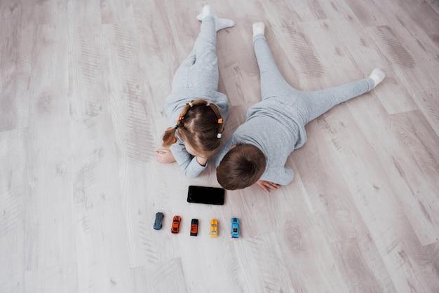 Ansicht von oben. kinder, die zu hause digitale geräte verwenden. bruder und schwester im schlafanzug schauen sich zeichentrickfilme an und spielen auf ihrem technologietablett Premium Fotos