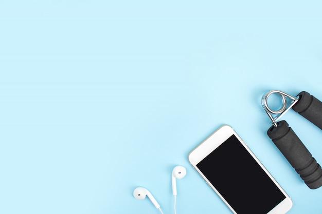 Ansicht von oben. sportzubehör mit hanteln, smartphones, kopfhörer in einem blau. mit textfreiraum. Premium Fotos