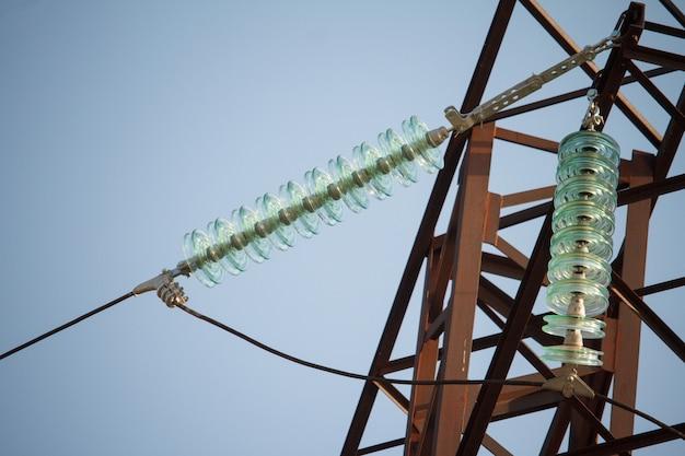 Ansicht von unten der nahaufnahme von isolatoren auf hochspannungsdrähten auf einem energieturm gegen einen blauen himmel Premium Fotos