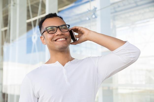 Ansicht von unten des lächelnden mannes sprechend am telefon am bürogebäude Kostenlose Fotos