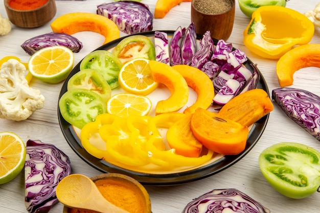 Ansicht von unten geschnittenes gemüse und obst kürbis persimone rotkohl zitronengrüne tomaten blumenkohl paprika auf runder platte verschiedene gewürze in kleinen schalen auf tisch Kostenlose Fotos
