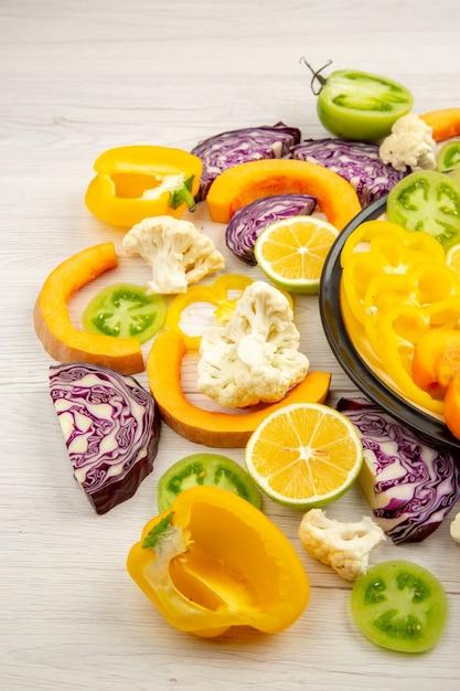 Ansicht von unten schneiden gemüse und obst kürbis gelbe paprika persimmon rotkohl grüne tomaten auf schwarzem teller auf holztisch Kostenlose Fotos