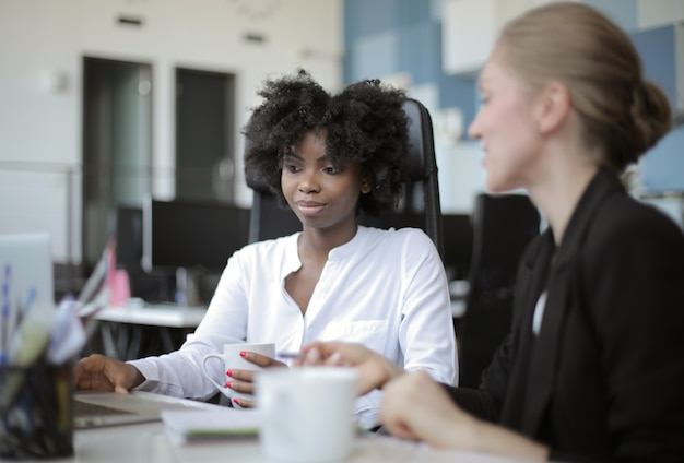 Ansicht von zwei weiblichen mitarbeitern, die nebeneinander in einem bürokonzept sitzen: rivalität, mitarbeiter Kostenlose Fotos
