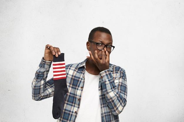 Anspruchsvoller junger afroamerikaner, der brille und hemd über weißem t-shirt trägt, das verschwitzte schmutzige stinkende socke in seiner hand hält und nase kneift, sein blick, der ekel mit unangenehmem geruch ausdrückt Kostenlose Fotos