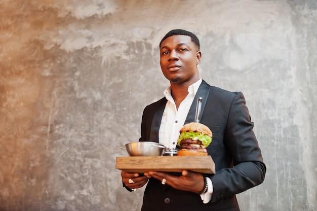 Anständiger junger mann im schwarzen anzug hält tablett mit doppeltem burger gegen graue wand Premium Fotos