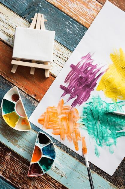 Anstrichausrüstung und unordentliches gemaltes papier auf hölzernem hintergrund Kostenlose Fotos
