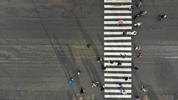 Antenne. asphaltstraße mit zebra fußgängerüberweg und menschenmenge. draufsicht. Premium Fotos