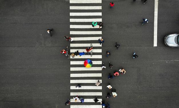 Antenne. menschen drängen sich auf fußgängerüberweg. zebrastreifen, draufsicht. eine person aus der menge hält einen bunten regenschirm. Premium Fotos