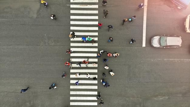 Antenne. menschen drängen sich auf fußgängerüberweg. zebrastreifen, draufsicht. Premium Fotos