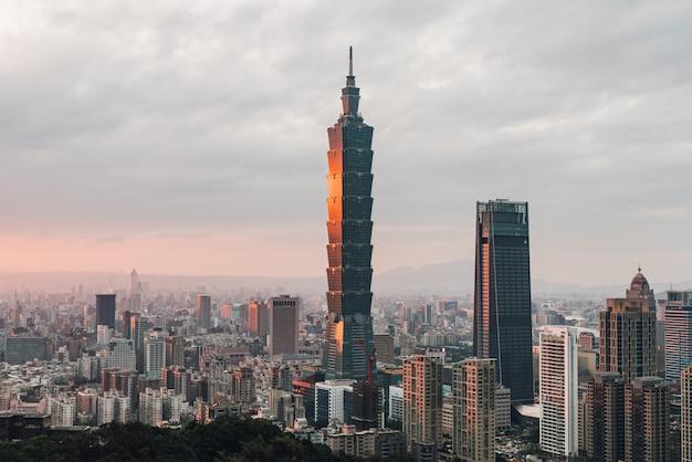 Antenne über im stadtzentrum gelegenem taipeh mit wolkenkratzer taipehs 101 in der dämmerung vom xiangshan-elefantenberg am abend. Premium Fotos