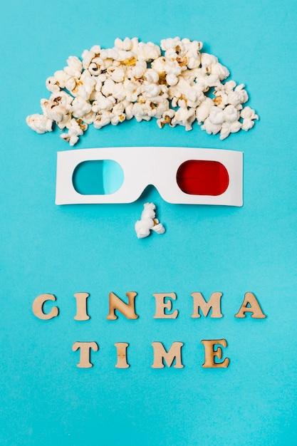 Anthropomorphes gesicht gemacht mit popcorn und gläsern 3d über dem kinozeittext gegen blauen hintergrund Kostenlose Fotos