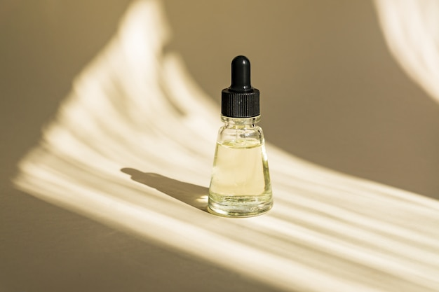 Anti-aging-serum in glasflasche mit tropfer an beiger wand. gesichtsflüssigkeit essentiell mit kollagen und peptiden Premium Fotos