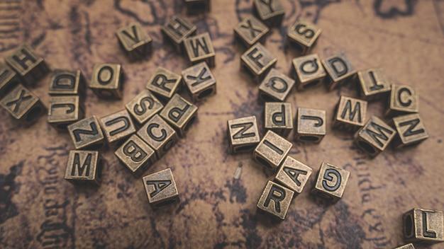 Antike bronze alphabete auf der alten weltkarte Premium Fotos
