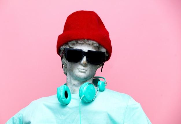 Antike büste des mannes im hut mit kopfhörern und sonnenbrille Premium Fotos