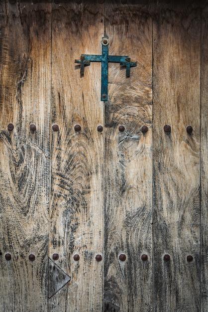 Antike holztür, verziert mit einem gusseisenkreuz und eisenstiften Premium Fotos