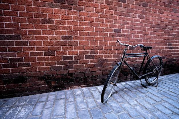 Antikes fahrrad mit hintergrund des roten backsteins. vintage-konzept Premium Fotos