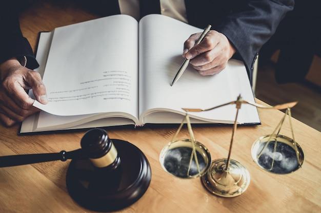 Anwalt oder richter, der mit vertragspapieren, dokumenten, hammer und waage der gerechtigkeit arbeitet Premium Fotos