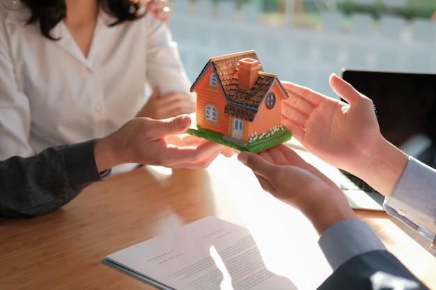 Anwalt versicherungsmakler geben hausmodell, um kunden zu koppeln. makler, der immobilien verkauft. kauf miethaus konzept. Premium Fotos