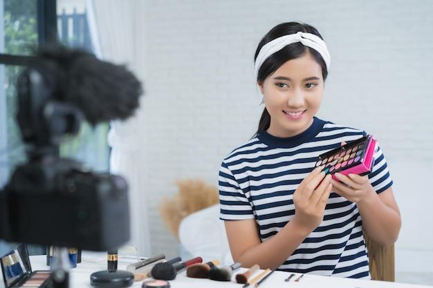 Anwesende schönheitskosmetik des schönheitsbloggers beim sitzen in der vorderen kamera für videoaufzeichnung Kostenlose Fotos