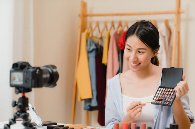 Anwesende schönheitskosmetik des schönheitsbloggers, die in der vorderen kamera für videoaufzeichnung sitzt. Kostenlose Fotos