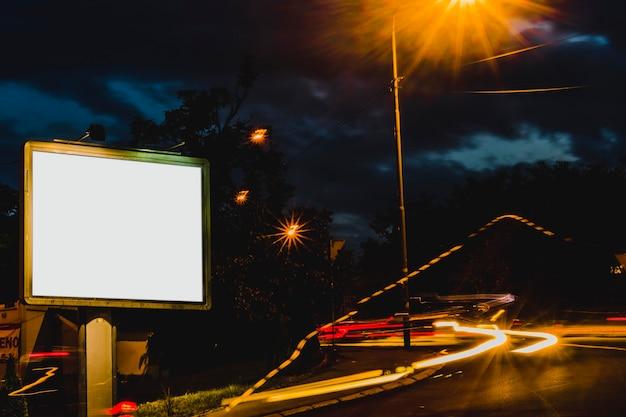 Anzeige billboard mit verschwommenen ampeln in der nacht Kostenlose Fotos