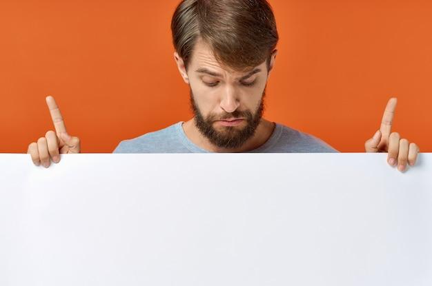 Anzeigenplakat in den händen eines mannes auf einem orangefarbenen hintergrund, der mit seinen händen gestikuliert, raummodell kopieren. hochwertiges foto Premium Fotos