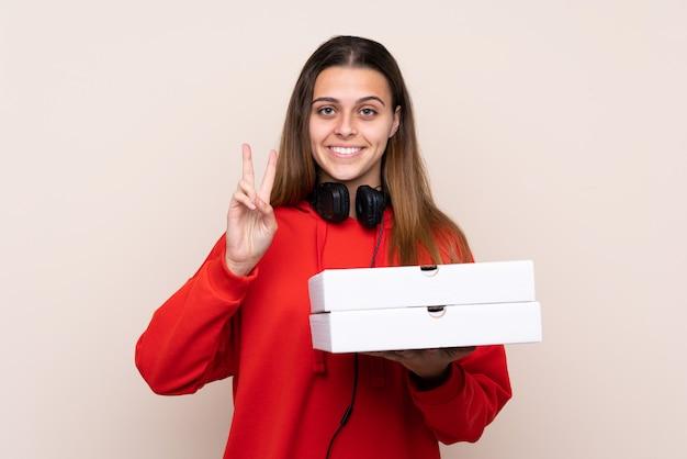 Anziehende pizzakästen des mädchens über lokalisierter wand Premium Fotos