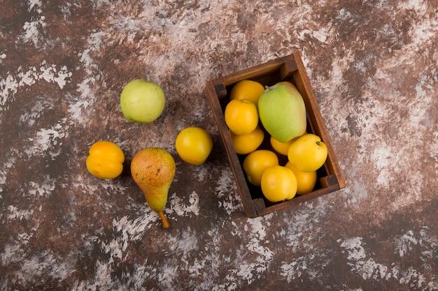 Apfel, birne und pfirsiche in einer holzkiste, draufsicht Kostenlose Fotos
