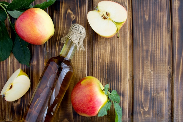 Apfelessig apfelwein in der glasflasche auf der braunen holzoberfläche. Premium Fotos