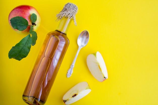 Apfelessig apfelwein in der glasflasche auf der gelben oberfläche. Premium Fotos