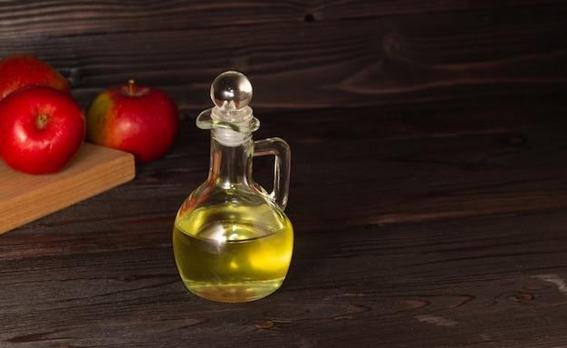 Apfelessig in einer glaskaraffe auf einem dunklen holztisch Premium Fotos
