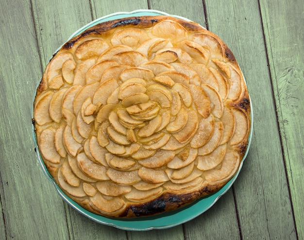 Apfelkuchen auf einem grünen holztisch Premium Fotos