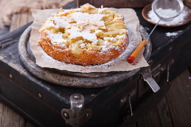 Apfelkuchen auf einem weinlesekoffer in puderzucker. Premium Fotos